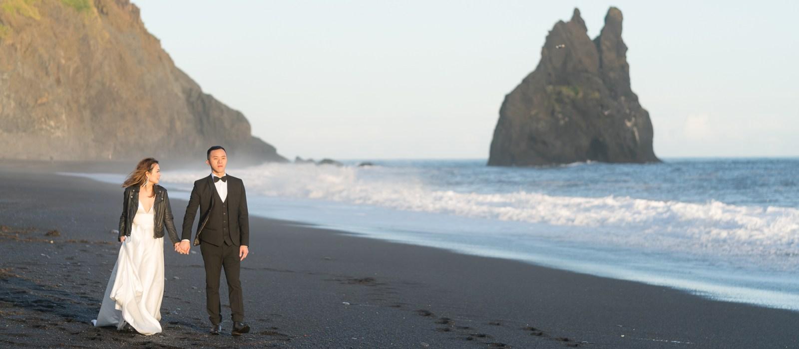 Couple walking on the Black Sand Beach near Vik, Iceland