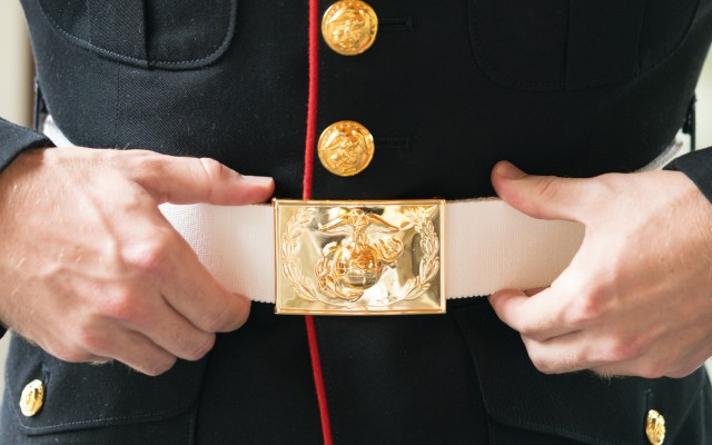 A Marine adjusts his belt prior to a National Museum of the Marine Corps wedding ceremony