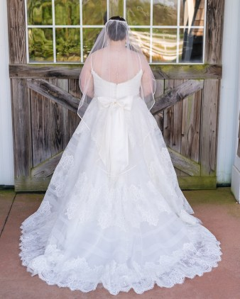 A bride shows off her Allure Bridals dress before her wedding at Hermitage Hill Farm in Waynesboro, Virginia.