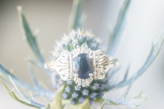 A vintage engagement ring photographed in the bride's bouquet.
