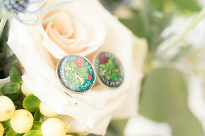 Sixpence cufflinks photographed against the bride's bouquet of white roses.