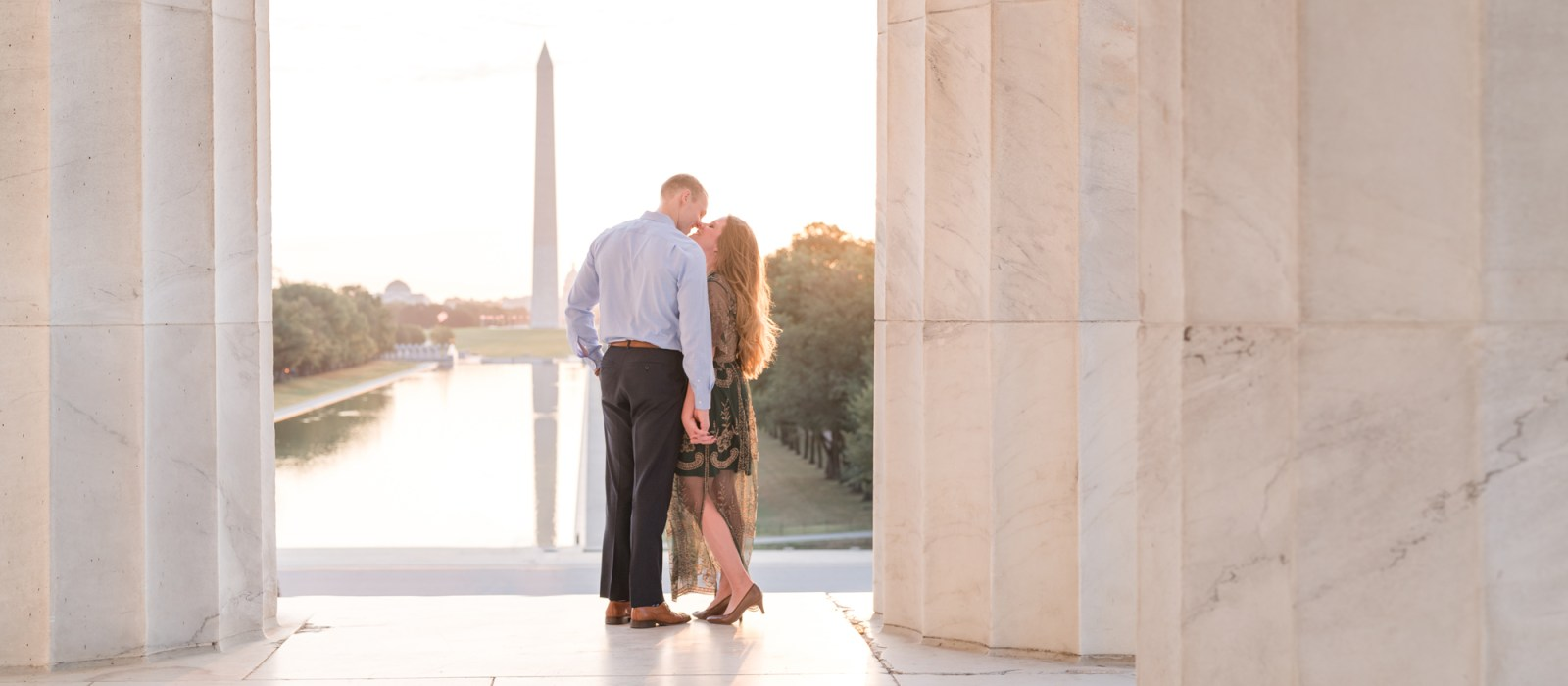 A couple holds hands and kisses during their Washington DC engagement session at the Lincoln memorial