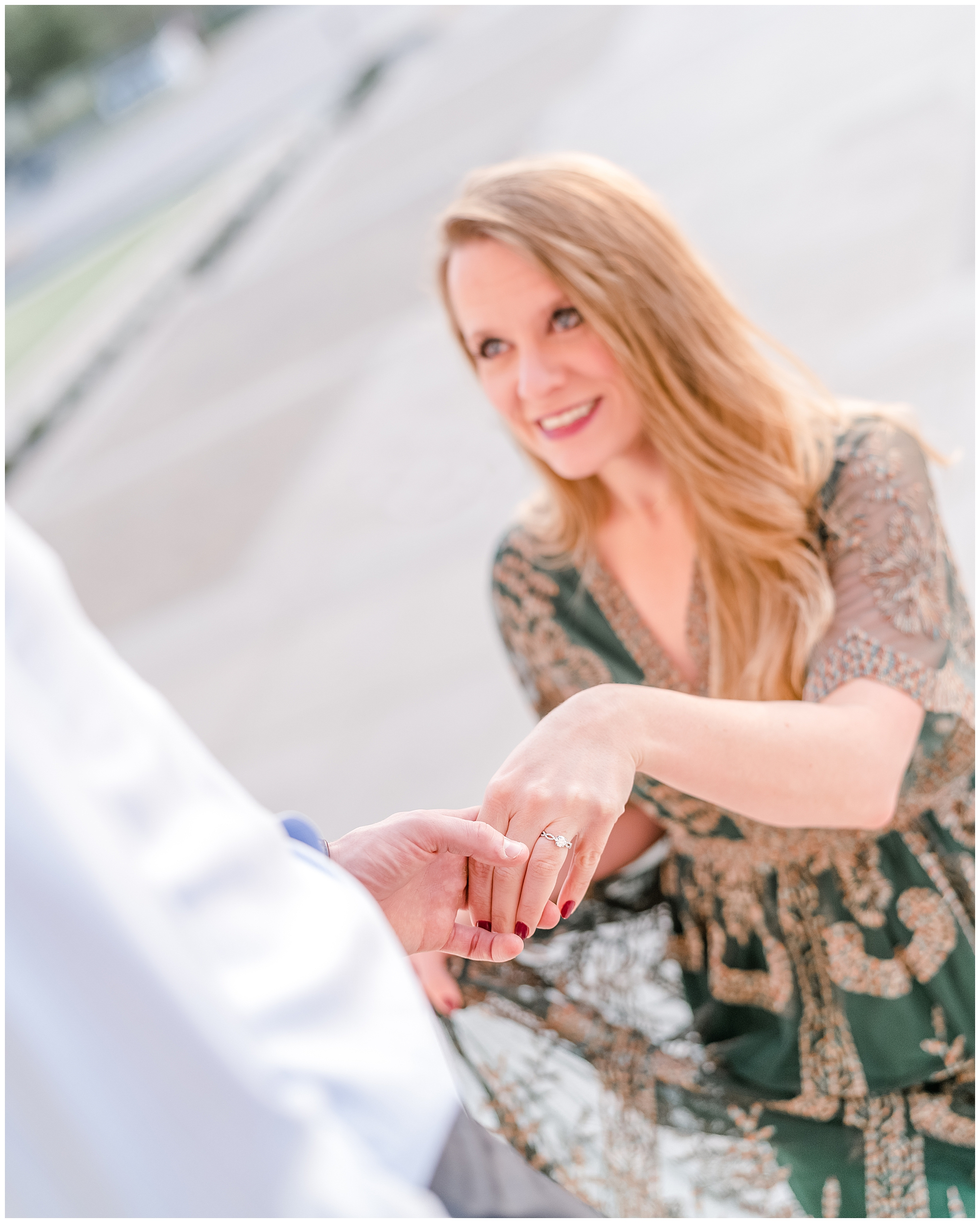 Engaged woman wearing a green dress smiles up at her fiancé while holding his hand during an engagement session.