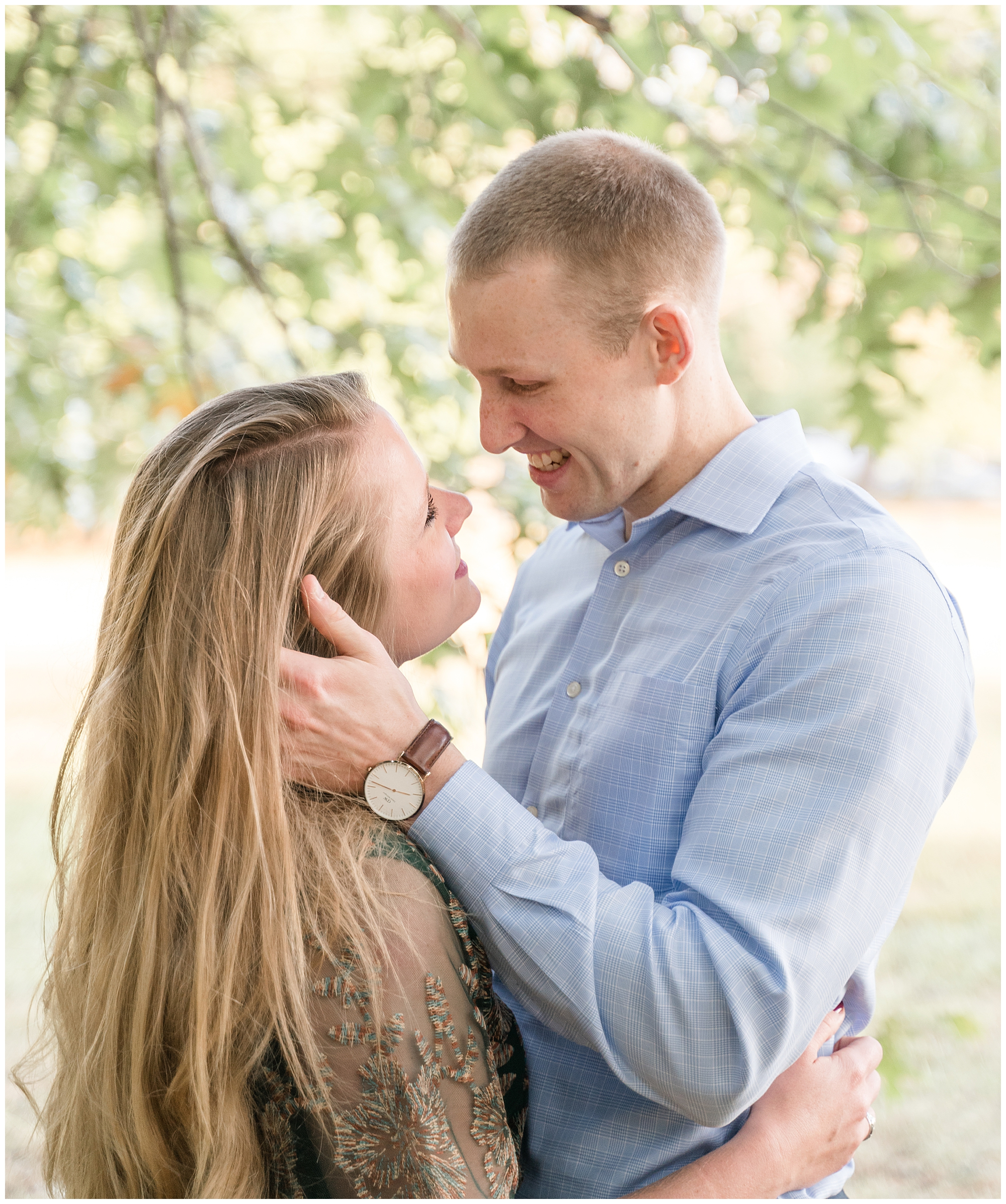 A man touches his fiancée's hair as they look at each other during their DC engagement session.