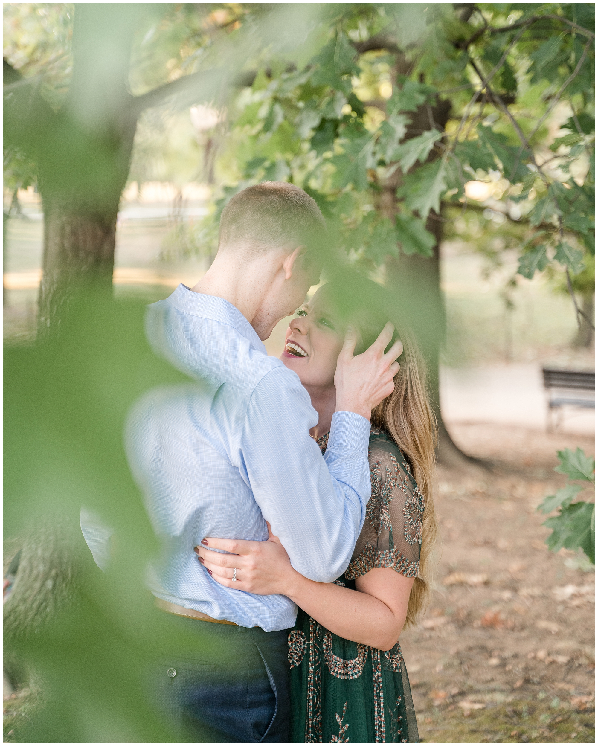 A man touches his fiancée's hair as they look at each other during their engagement session.