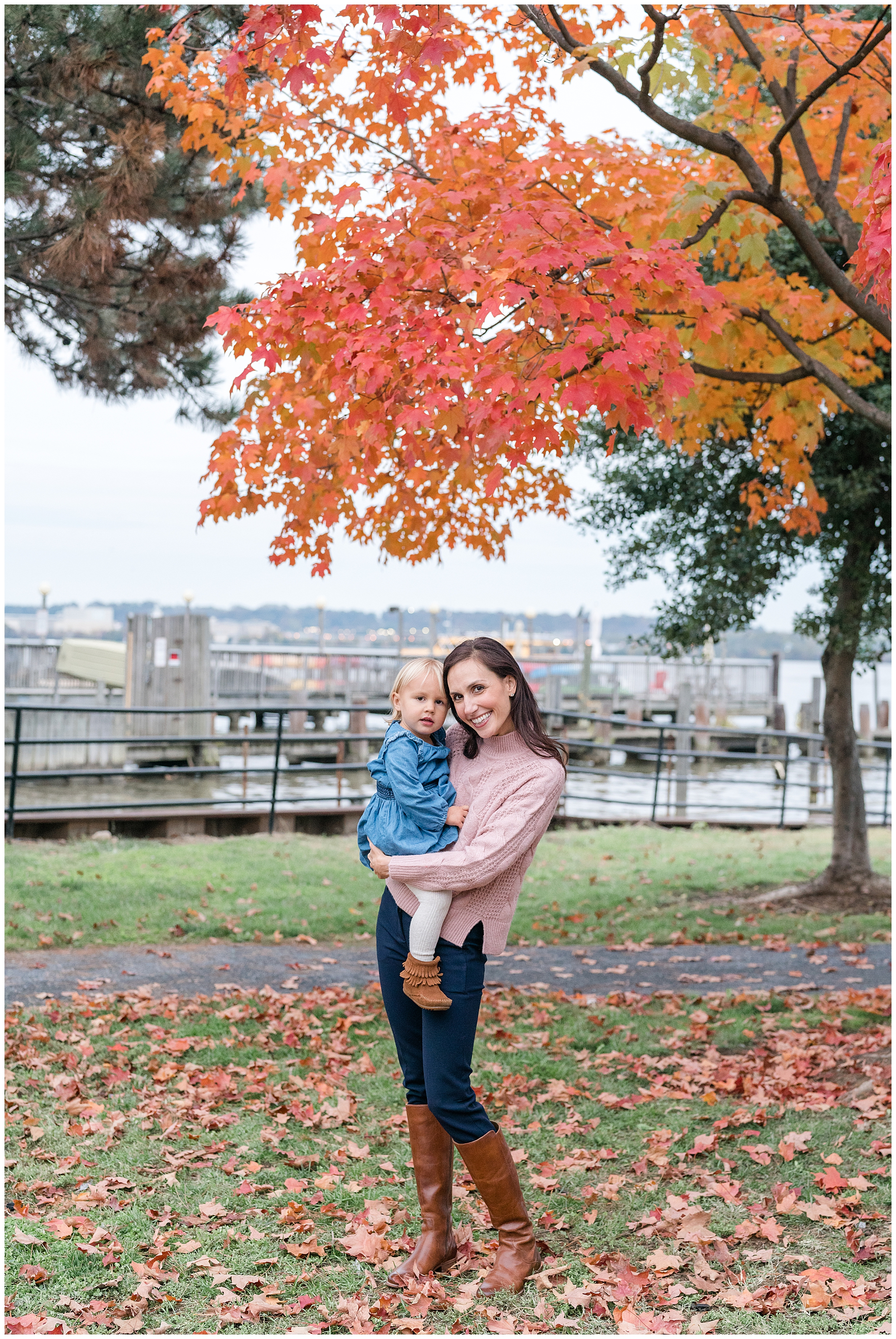 A mom holds her toddler daughter under bright red leaves during a fall family photography session in Alexandria, Virginia.