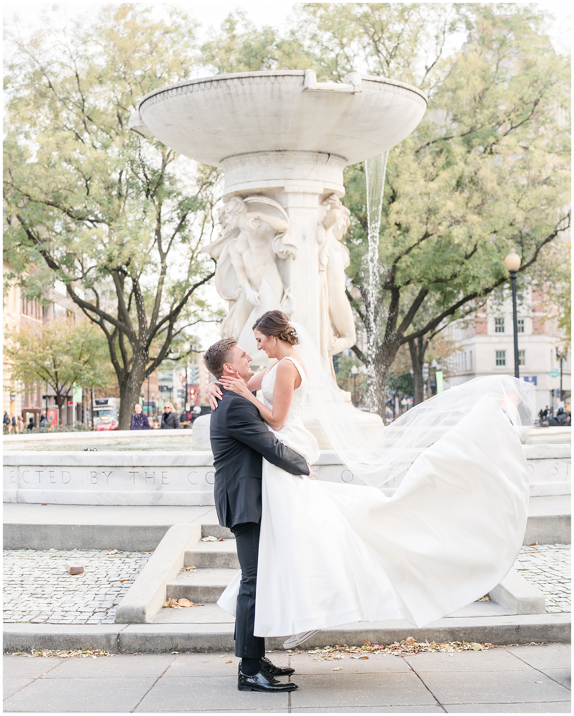 A groom lifts his bride in DuPont Circle during their Washington DC wedding