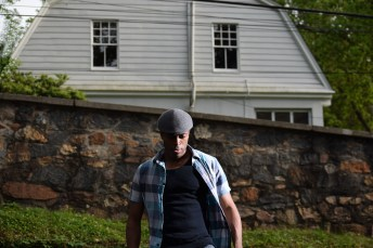 Directional light used on the left side of a man, who stands in front of a stone wall that slants diagonally to his left.