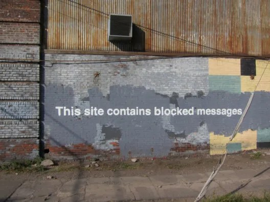 "Banksy's ""This site contains blocked messages,"" an artwork completed during his much-publicized stay in New York. Image © <a href='https://www.flickr.com/photos/scottlynchnyc/10526310184/'>Flickr user scottlynchnyc</a> licensed under <a href='https://creativecommons.org/licenses/by-sa/2.0/'>CC BY-SA 2.0</a>"
