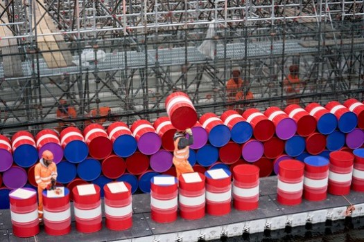 Workers installing barrels on the vertical side of the London Mastaba. Image © Wolfgang Volz