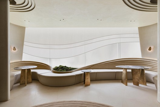 A series of undulating curves are recurring motifs and provide an abstract echo of nature. Lines are cut into the plaster of the ceiling in patterns that suggest raked gravel patterns of a sand garden, while organically shaped sconces and tables are designed to mimic rocks in a garden. Image © Harold De Puymorin