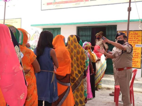 मतदाताओं को प्रयागराज में सामाजिक दूरी का पाठ पढ़ाते पुलिस अधिकारी।