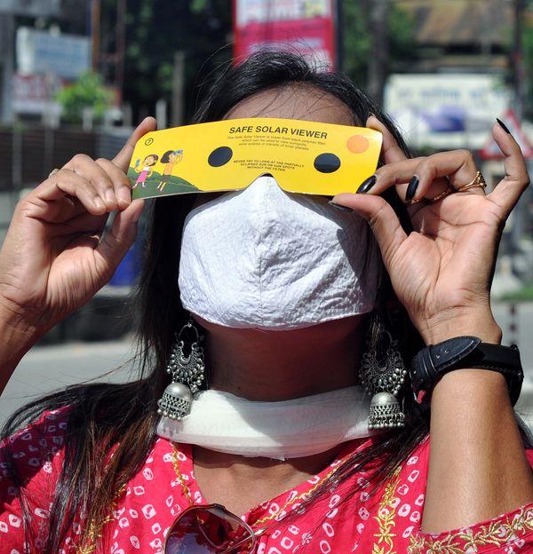 गुवाहाटी में सूर्यग्रहण का शानदार नजारा देखती एक महिला।