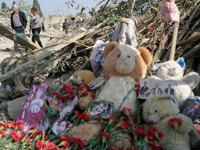 गांजा शहर में शनिवार को हुए रॉकेट हमले के बाद मरने वाले बच्चों और लोगों को याद करते हुए टेडी बियर और तस्वीरें रखी गईं।