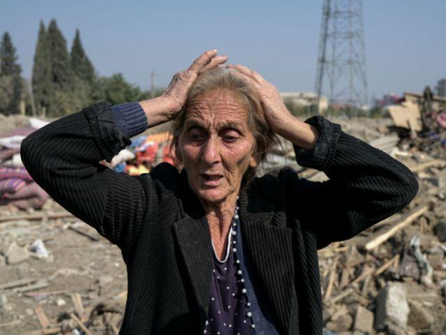 इस फोटो में 67 साल की रेजि गुलुयेवा गांजा शहर में हुए रॉकेट हमले में खंडहर बने अपने घर के ऊपर खड़ी नजर आ रही हैं।