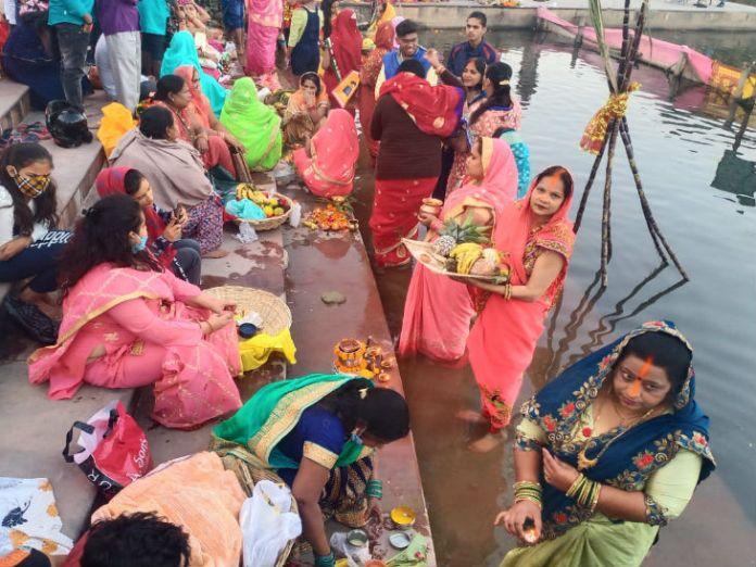 लक्ष्मण मेला मैदान में बने छठ घाट पर नदी में खड़ी महिलाएं।