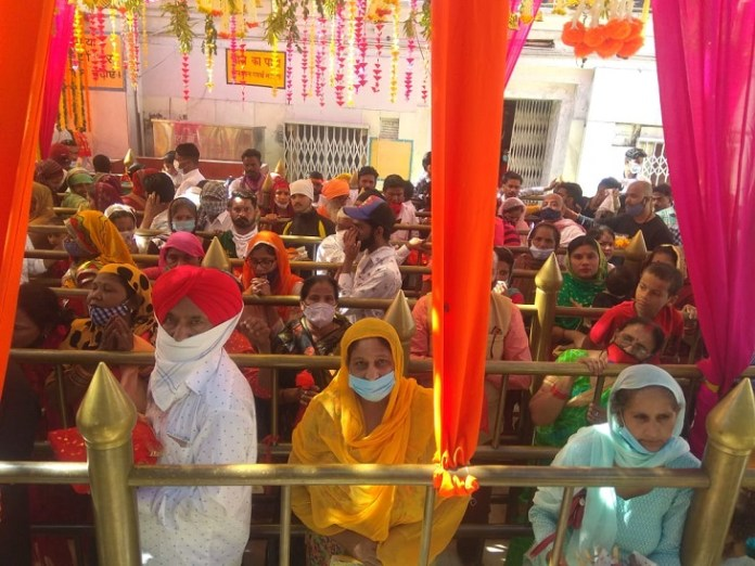 Devotees standing in lines to bow their heads.