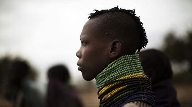 A Kenyan woman watches much-needed rain fall in the Turkana region. Kenyan parliament has approved a bill allowing men to marry as many women as they want, leaving wives with no right to stop them.