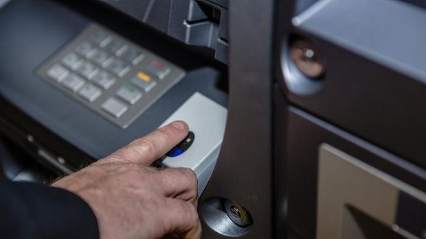 Mr Masters keys in information using the ATM. Photo by: Jamila Toderas