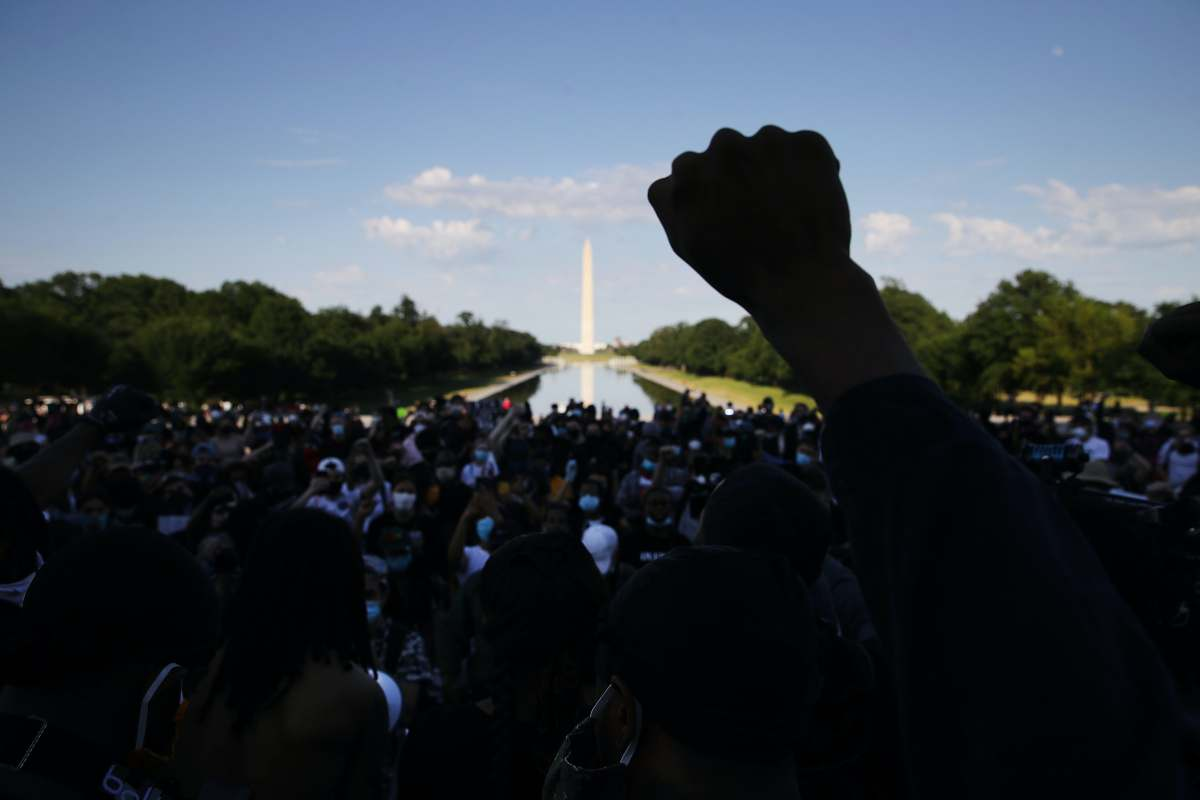 A demonstrator at the Lincoln Memorial during a peaceful protest against police brutality and the death of George Floyd, on June 2, 2020 in Washington, DC. | Source: Getty Images