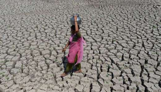 A woman walks on the parched bed of Chandola Lake with a metal pot on her head to fetch water in Ahmedabad on 20 May 2016. India is facing its worst water crisis in decades, with about 330 million people  suffering from drought