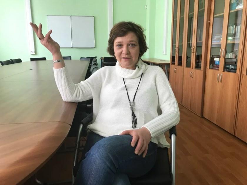Jelena Panfilova istuu ja nostaa oikeaa kättään ilmaan katsoen kameraan.