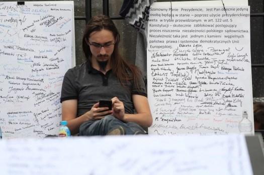Nimiä suurilla paperella, mies istuu vetoomusten edessä ja lukee kännykkää.