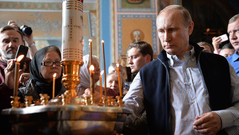Vladimir Putin sytyttää kynttilän Valamon luostarissa.