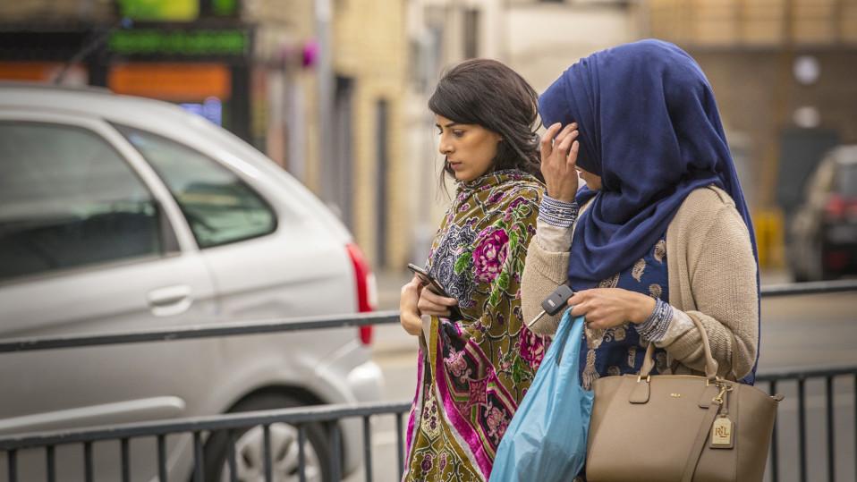 Intialaista huivia harteillaan pitävä nainen, jolla on pää paljaana. Hänen vieressään on tummansiniseen intialaiseen päähuiviin verhoutunut nainen.