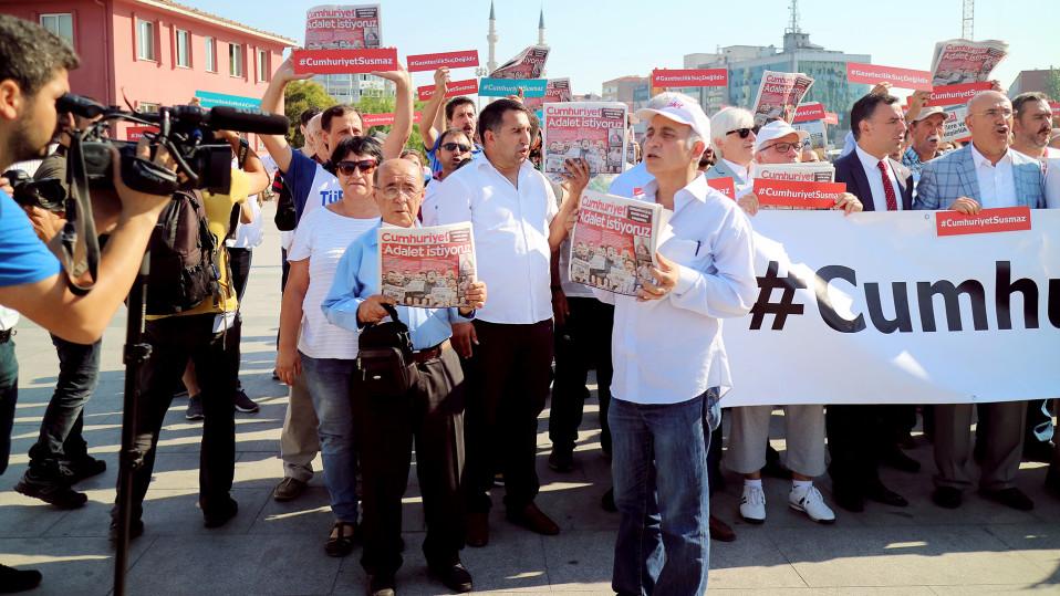 Mielenosoittajat pitävät kädessään päivän Cumhuriyetia. Lehden etusivulla vaaditaan vapautta lehden toimittajille.