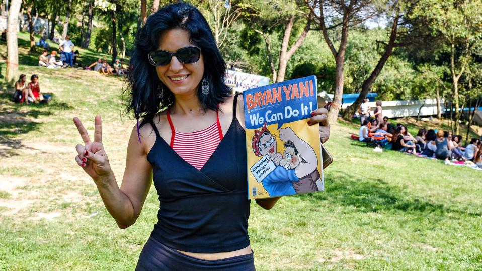 Feministisen sarjakuvalehden toimittaja Arzu Çakmaklilla on vasemmassa kädessään sarjakuvalehti ja oikeassa hän näyttää voitonmerkkiä.