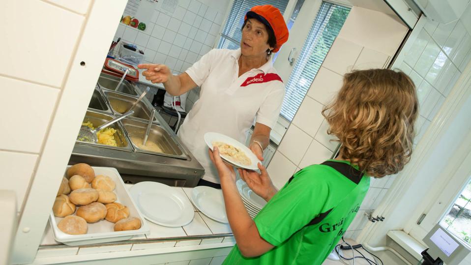 keittäjä antaa ruokaa oppilaalle