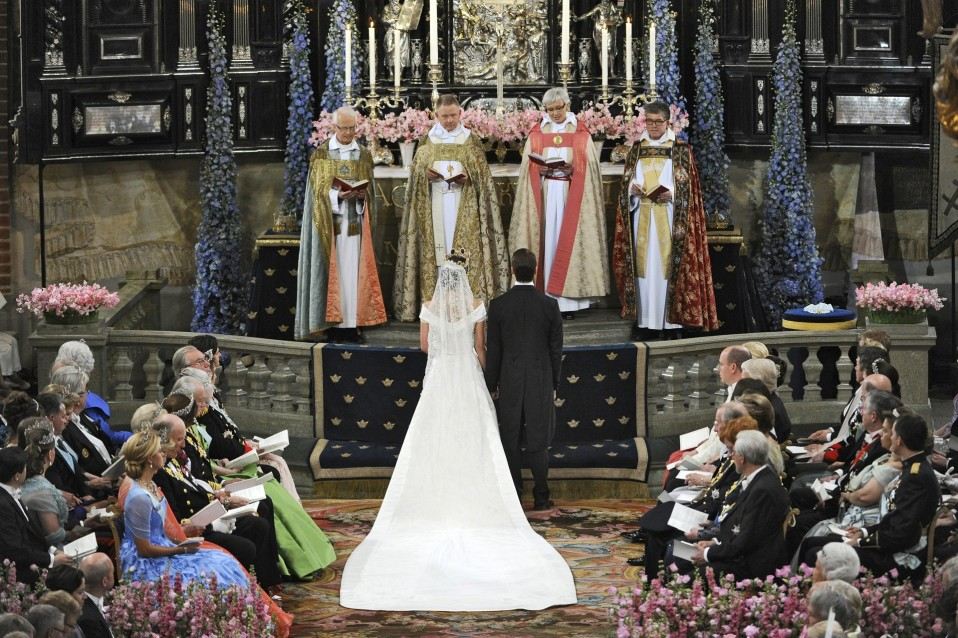 Victoria ja Daniel selät kameraan päin, edessään alttari ja papit.