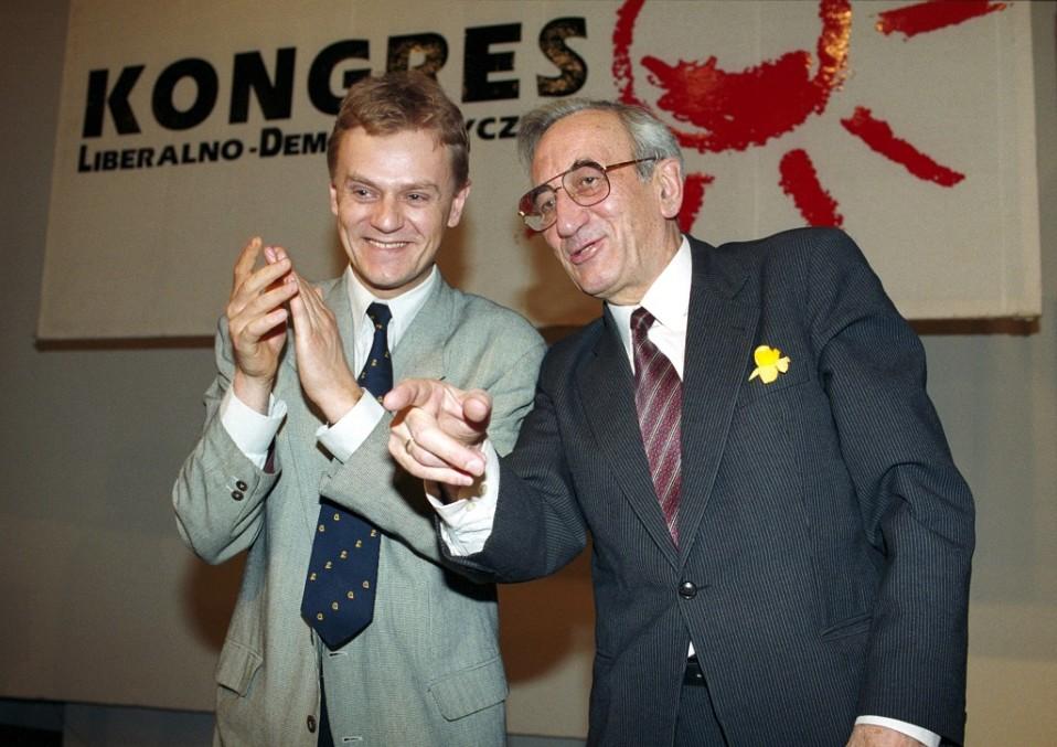 Kuvassa ovat itäblokin ensimmäiseksi ei-kommunistiseksi pääministeriksi Puolassa noussut Tadeusz Mazowiecki ja nuori Donald Tusk. Mazowiecki on oikealla ja osoittaa oikealla kädellään eteenpäin. Tusk taputtaa hänen vieressään.