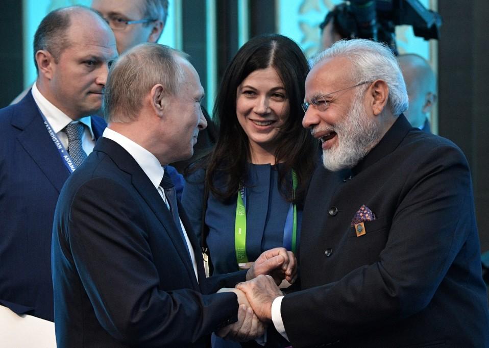 Putin ja Modi kättelevät, Putin hymyilee, Modi nauraa.
