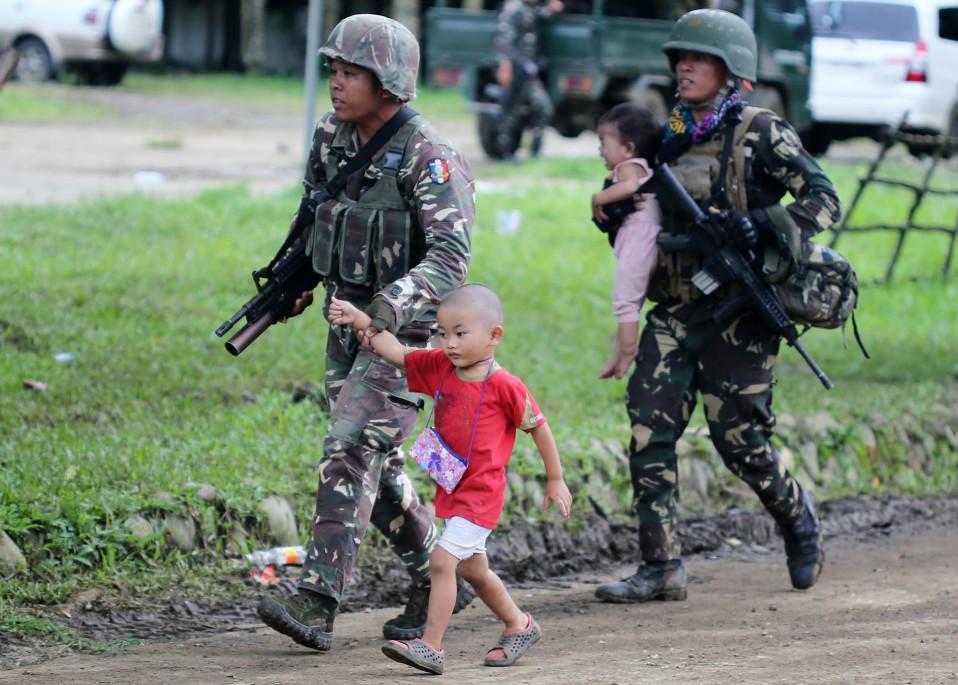 Hallituksen sotilaat vievät pakenevia lapsia turvaan.