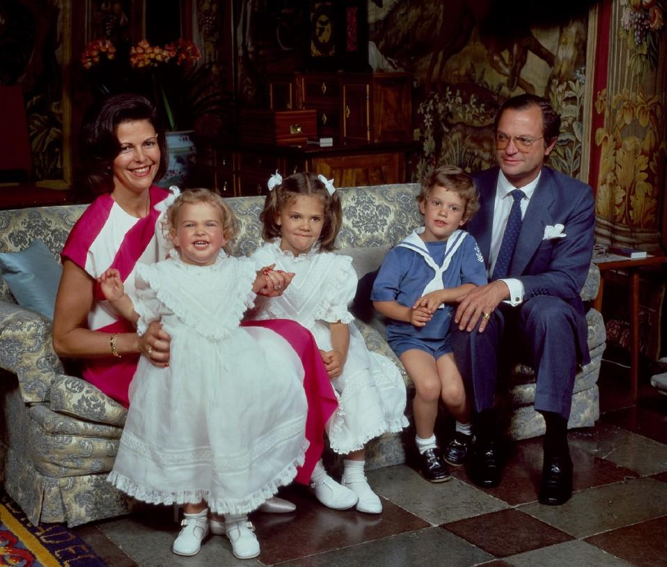Madeleine istuu kuningatar Sylvia sylissä, vieresssa Victoria (kesk.), Carl Philip ja kuningas Kaarle Kustaa (oilk.)