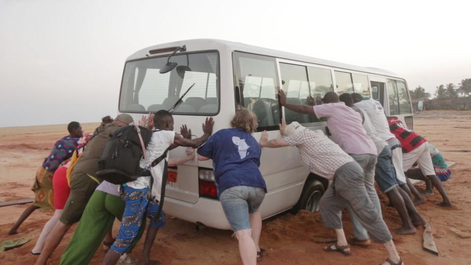 Joukko ihmisiä työntää hiekkaan juuttunutta minibussia Beninissä.
