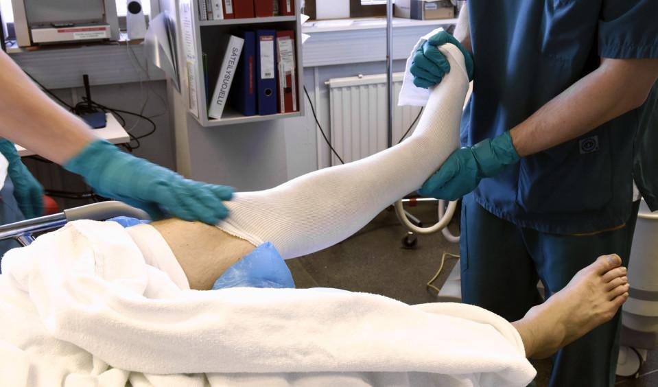 Lääkintävahtimestari kipsaa miehen jalkaa Töölön tapaturma-asemalla Helsingissä.