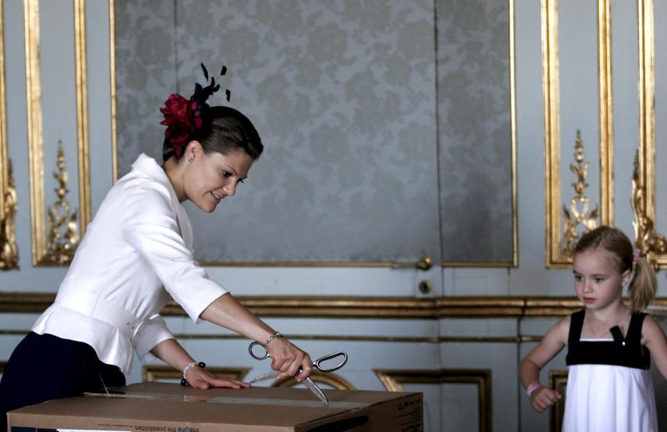 Victoria avaa saksilla suurta pahvilaatikkoa.