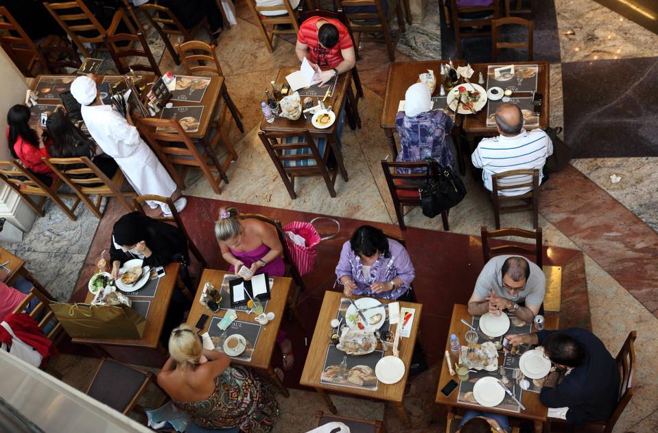 Ihmisiä ruokailemassa Dubailaisessa ravintolassa. Kuva ylhäältä.