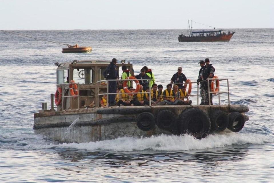 Australian maahanmuuttoviranomaiset kuljettavat pakolaisia veneen kannella.