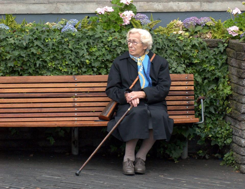 Eläkeikäinen nainen istumassa puistonpenkillä.
