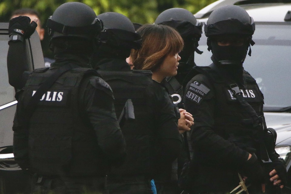 Mustiin pukeutuneita ja kypäräpäisiä poliisieja, keskellä nuori nainen