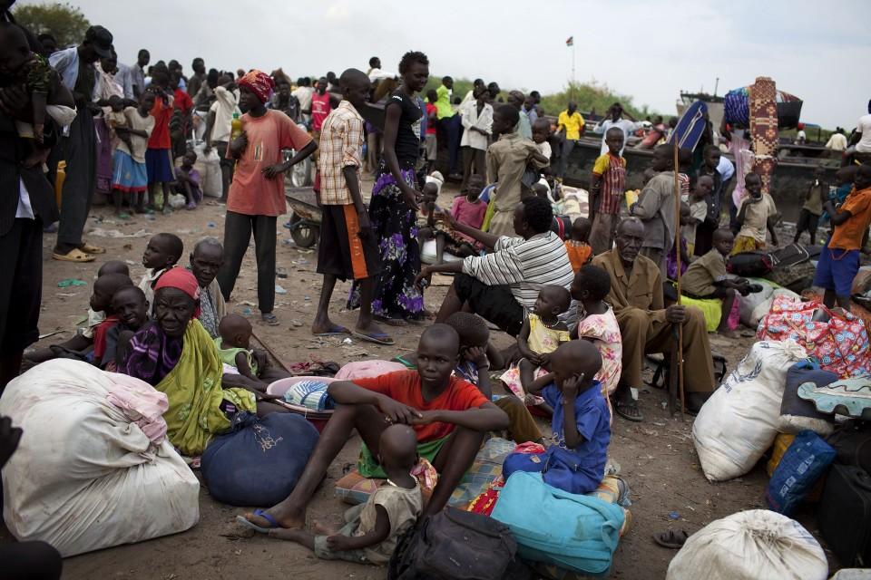 Iso joukko pakolaisia istuu tai seisoo aukiolla nyyttejä mukanaan.