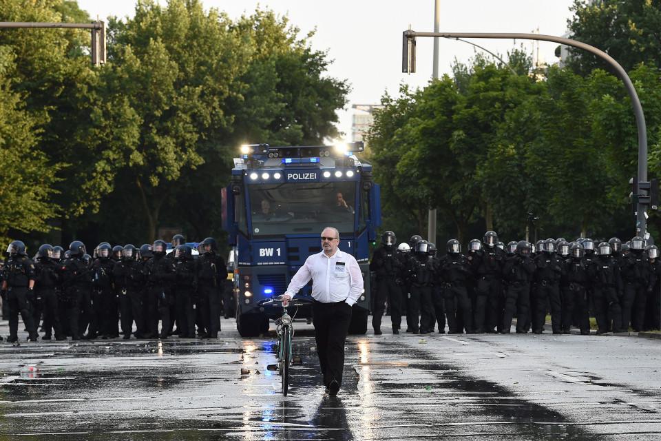 Mies taluttaa pyöräänsä mellakkapoliisien ohi.