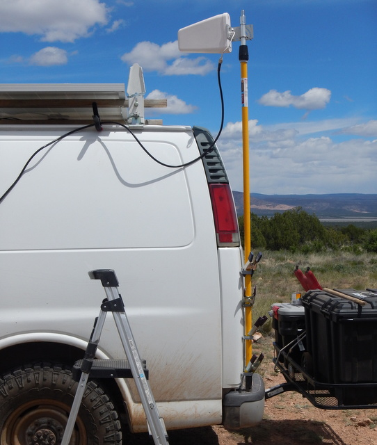 I mounted the antenna on a 6 to 12 foot painter pole. Here it's in the down position because it was a windy day. With just a twist I an raise it to 12 feet. The cell tower is on the far ridge-line just above Interstate 40.