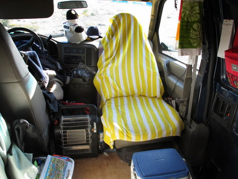 In this picture we are looking forward at the driving area. Notice that Sarah has turned her passenger seat around which gives her a very comfortable recliner to lounge in. To make a van a home it must be a comfortable place to hang around in and turning the seat makes that easy. The little cooler is her footrest. There's no way to be comfortable if you are cold so you can see her Mr. Buddy portable heater between the seats.