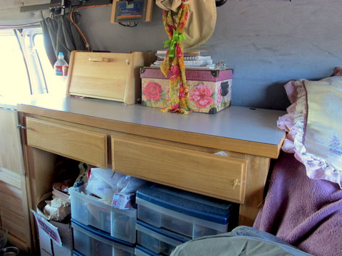 Here is another cheap desk from a thrift store. She  measured them carefully to make sure they would fit over her wheel-wells. Not wanting to wast e any space she put plastic drawers under the desk in front of the wheel-well.