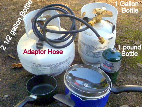 In this photo you see a 2 1/2 gallon and 1 gallon propane bottle, an adapter hose, and a small, green 1 pound bottle. I've since replaced the 1 gallon bottle for a 5 gallon bottle in preparation for Peak Oil.